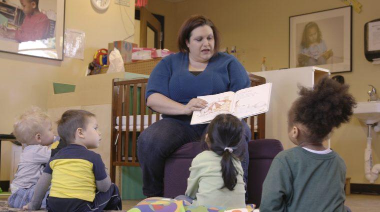 YWCA volunteer reads to children in childcare